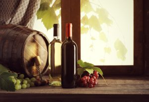 Wine bottles with grapes and barrel on old wooden table
